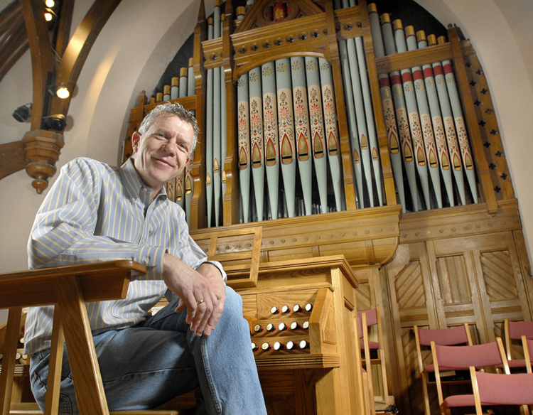 Ray Cornils, municipal organist for the city of Portland, at the organ of First Parish Church in Brunswick, where he is music director. The growth in praise-band led services, combined with a nationwide shortage of qualified organists, is prompting many congregations to leave pipe organs out of their new construction plans.