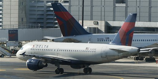 FILE- In this Tuesday, Jan. 24, 2012, file photo, a Delta Airlines plane taxis past a gate at Logan Airport in Boston. (AP Photo/Charles Krupa, File)