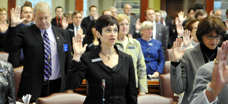 Gay Grant, D-South Gardiner, center, takes the oath of office Wednesday as a state representative at the House in Augusta. All Senate and House members were sworn in for the 126th Legislature by Gov. Paul LePage.