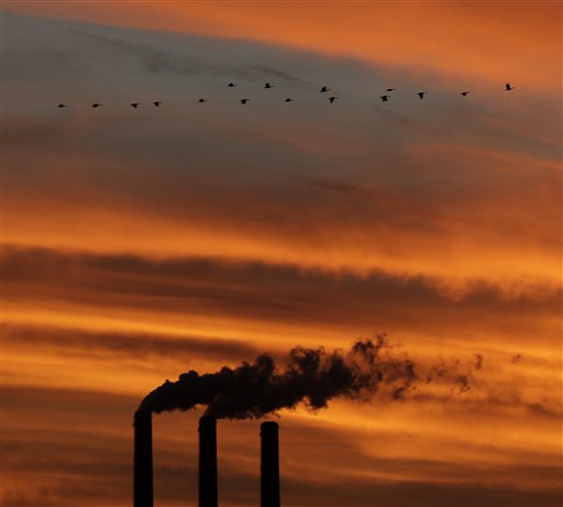 Geese fly past the smokestacks at the Jeffrey Energy Center coal power plant as the sun sets near Emmett, Kan.