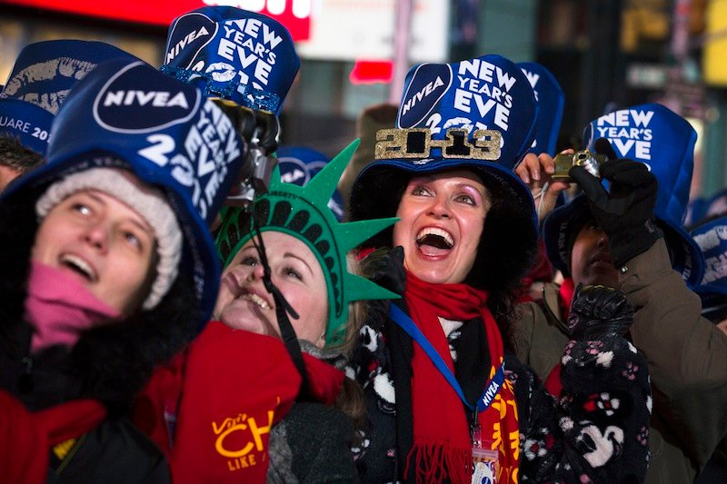 Olga Lovchu, of Chicago, center right, cheers in Times Square for the New Year's Eve celebration, Monday, Dec. 31, 2012, in New York. This will be the first Times Square countdown in decades without Dick Clark, who died in April, and will be honored with a tribute concert and his name printed on pieces of confetti. (AP Photo/John Minchillo)
