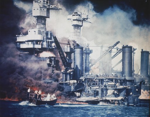 In this U.S. Navy file photo, a small boat rescues a USS West Virginia crew member from the water after the Japanese bombing of Pearl Harbor on Dec. 7, 1941. Two men can be seen on the superstructure, upper center. The mast of the USS Tennessee is beyond the burning West Virginia.