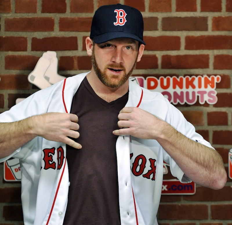 New Boston Red Sox pitcher Ryan Dempster puts on his jersey during a baseball news conference, Wednesday,in Boston. Dempster and the Red Sox finalized a two-year, $26.5 million contract.