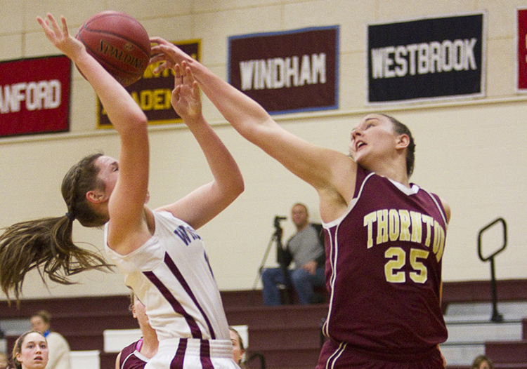 Olivia Shaw of Thornton Academy knocks away a shot by Haley Batchelder of Windham during their SMAA schoolgirl basketball game Friday at Windham. Thornton went 1 of 11 from the foul line in the final minute and a half but came out with a 37-36 win.