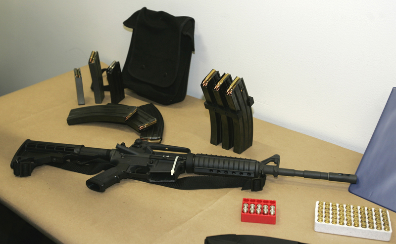 This March 27, 2006, file photo shows a Bushmaster AR-15 semi-automatic rifle and ammunition on display at the Seattle Police headquarters in Seattle.