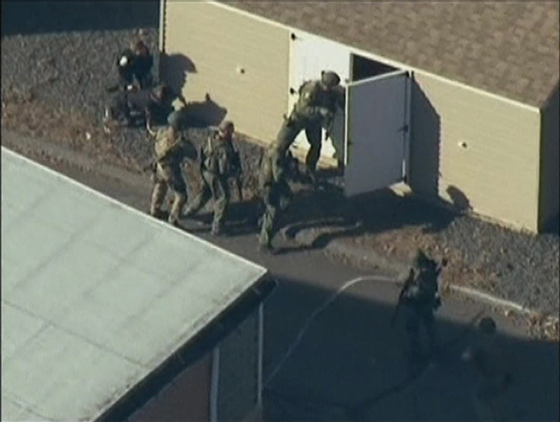 Police search a building after the shooting at Sandy Hook Elementary School in Newtown, Conn., on Friday, Dec. 14. The president of the Maine Gun Owners Association says teachers with firearms training should be allowed to carry guns following the Connecticut shooting in which 20 elementary school children were killed.