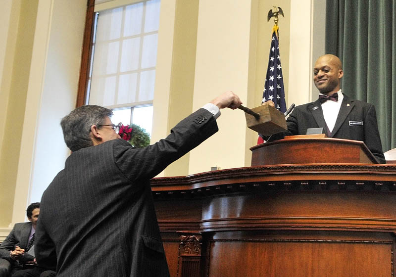 Maine Electoral College Secretary Roy Gedat, left, holds the ballot box to collect Maine Electoral College President Craig Hickman's vote on Monday, in the House chamber of the State House in Augusta. Hickman, a Democratic state representative from Winthrop, along with fellow Electoral College members Diane Denk, of Kennebunk, Marianne Stevens, of Kingfield, and Jill Duson, of Portland, cast four votes for Barack Obama as U.S. president and Joe Biden as vice president.