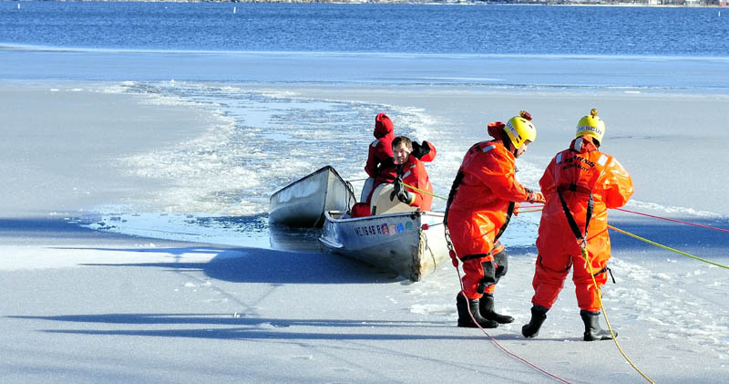 Area firefighters in survival suits drag a canoe to shore on North Pond in Mercer on Tuesday. Tracy Scott, 47, of Mercer, went out on the thin ice with the canoe to rescue a small dog and plunged into the water, but was later rescued.