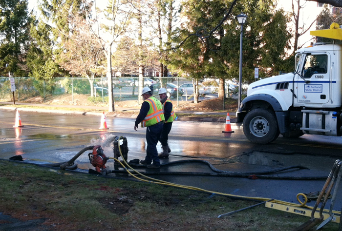 Workers on the scene of a water main break Monday on Pickett Street near Broadway in South Portland.