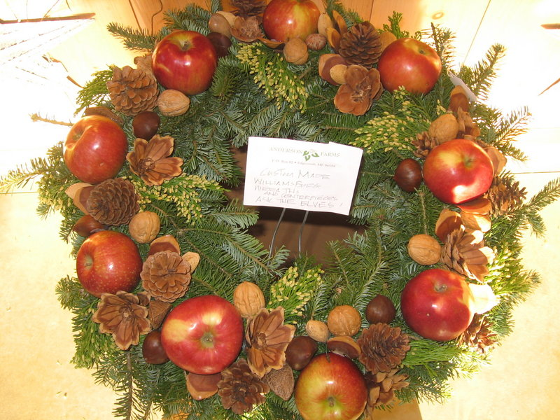 Greens and fresh fruit are joined by dried materials like pinecones and seed pods to make a Williamsburg wreath.