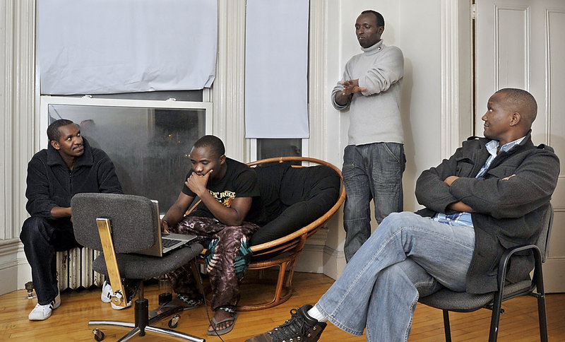 With the help of interpreter Damas Rugaba, right, immigrants from Rwanda, from left, Aristide Subikino, Isaac Ishimwe and Jean Bosco talk cold-weather issues, including communicating with the manager of their High Street apartments in Portland about heat.