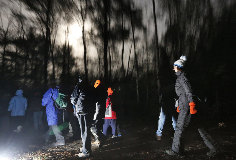 Chilly weather notwithstanding, a moonlight hike led by the Eastern Trail Alliance attracts several dozen hikers who quietly move on the path behind Kennebunk Elementary School to enjoy the woods, wildlife and night sky.