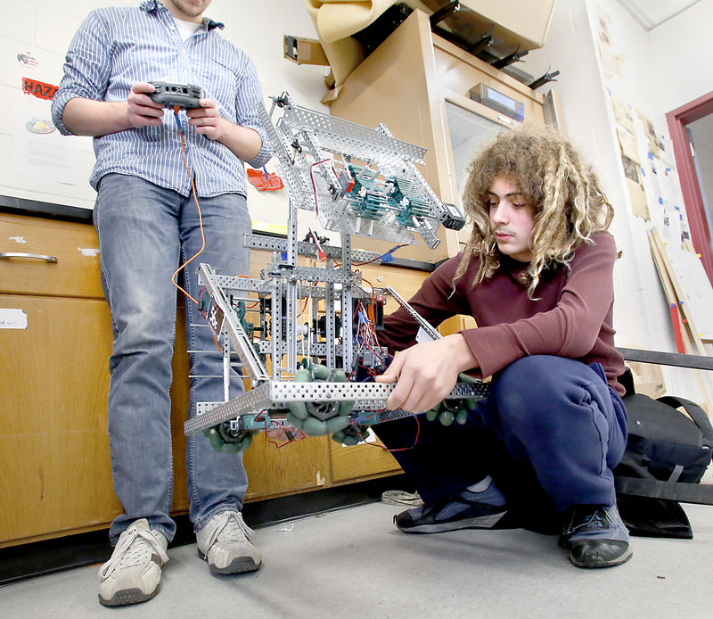 Matthew Reale-Hatem, 16, a junior, holds up a robot as Ian Schrank, also 16 and a junior, operates the controls as they troubleshoot a problem Friday.