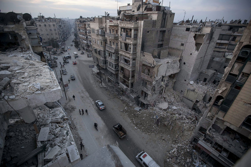 Destroyed buildings, including the Dar Al-Shifa hospital, are seen on a Sa'ar street Thursday after airstrikes targeted the area in Aleppo, Syria.