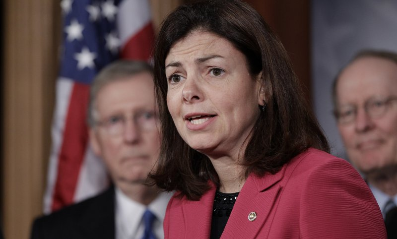 Sen. Kelly Ayotte speaks to the media with Senate Minority Leader Mitch McConnell in the background in 2014.