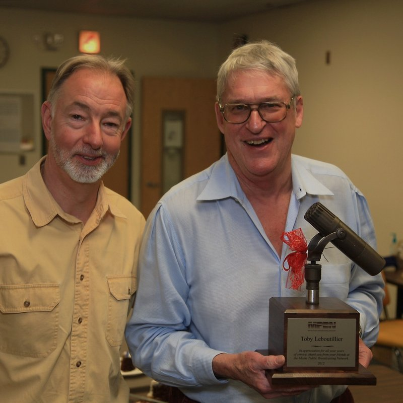 "MPBN program director Charles Beck, left, enjoys a moment with Toby Leboutillier, holding a microphone, after Friday's airing of ""Down Memory Lane."""