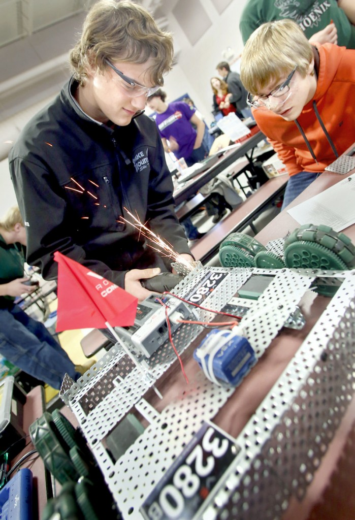 Camden Noll, 14, from Spruce Mountain High School, removes a piece from his team's robot as teammate James Herlihy, 14, looks on Saturday at the Southern Maine VEX Robotics Tournament.