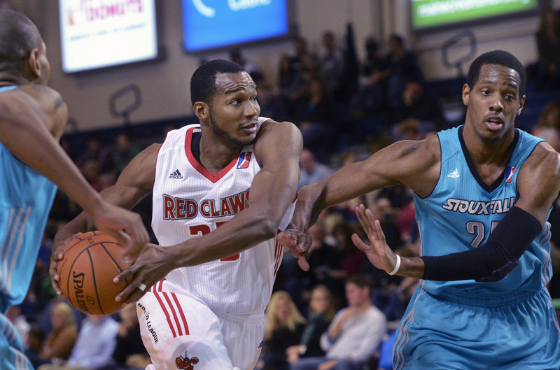 Chris Wright of the Red Claws drives to the hoop while Mike Davis of Sioux Falls tries to keep him at arm's length during Sunday's game in Portland, won by the Skyforce, 98-87.