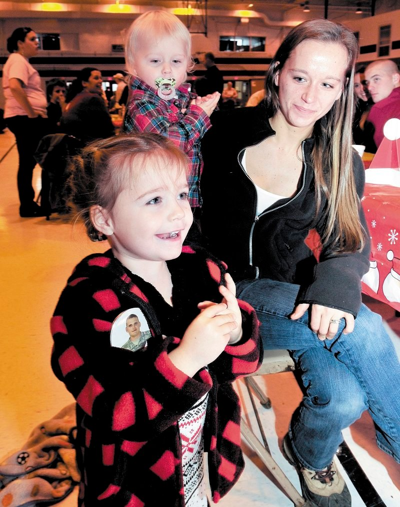 Cheyenne Allen, 3, of Strong, wearing a button with a photo of her father, Sgt. Sheldon Allen, reacts as Santa enters the Armory in Waterville on Sunday. With her are mother Emma and brother Elias.