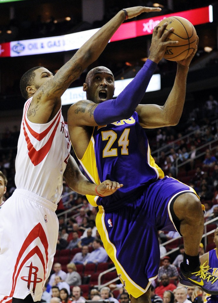 Kobe Bryant of the Lakers drives to the basket against Houston's Marcus Morris in Tuesday night's game at Houston. The Rockets rallied for a 107-105 win.