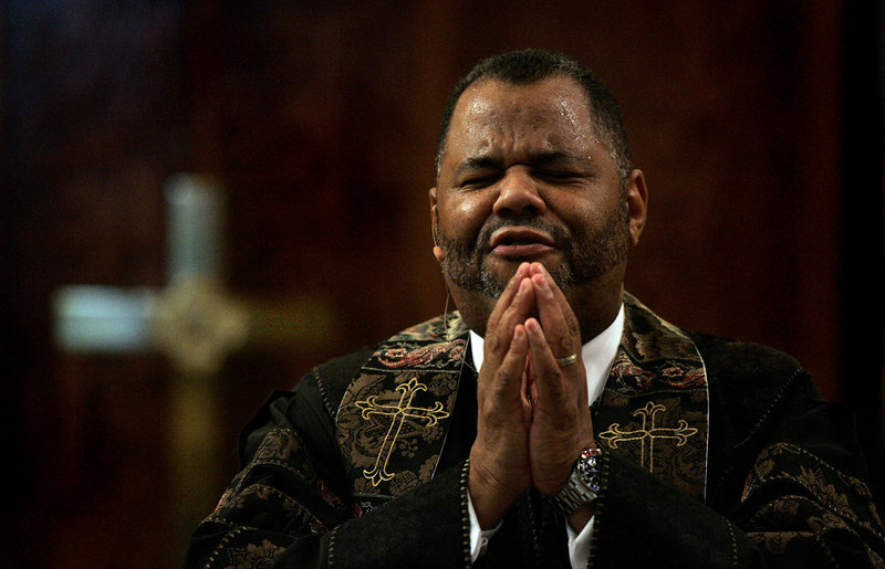 The Rev. John J. Hunter leads his congregation in prayer at First AME Church of Los Angeles on Aug. 15. He is fighting to regain his position, despite a civil suit against him.