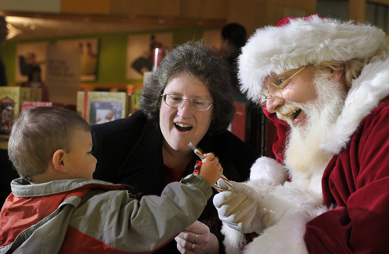 The roles are reversed as 2-year-old William Burke of Gray hands a candy cane to Santa as grandmother Elizabeth Burke watches at the Maine Mall in South Portland on Friday. This Santa replaces a previous one at the mall who drew some complaints.
