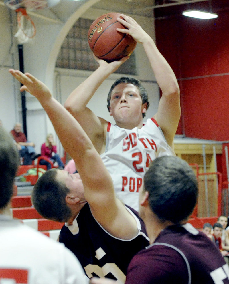 Conner MacVane of South Portland keeps his eyes on the basket while lofting a shot over Shaun Francoeur of Windham at Beal Gym.