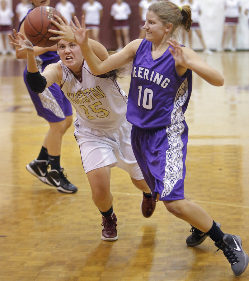 Emily Richard of Thornton Academy, left, lunges in an attempt to beat Sami Mack of Deering to a loose ball Friday night in Deering's 38-35 opening-night victory.