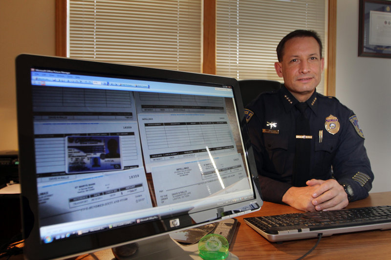 Tilton, N.H., Police Chief Robert Cormier shows images of counterfeit checks on his computer. He helped nab three men who passed more than $370,000 in counterfeit checks.