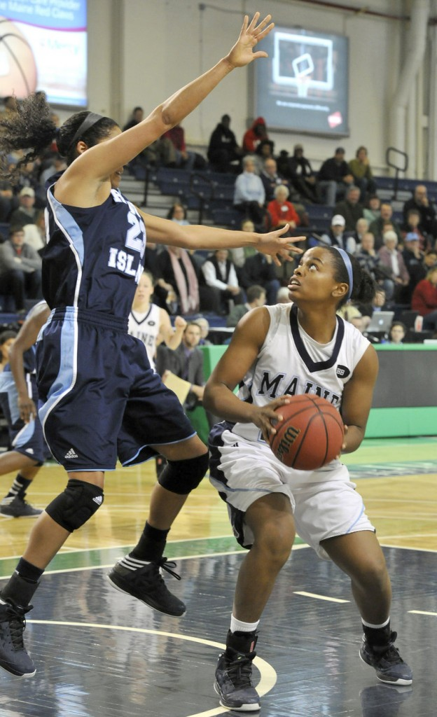 Ashleigh Roberts, who tried to get Maine back in the game by scoring 12 of her 14 points in the second half Saturday, looks to shoot against Brianna Thomas of Rhode Island at the Portland Expo.