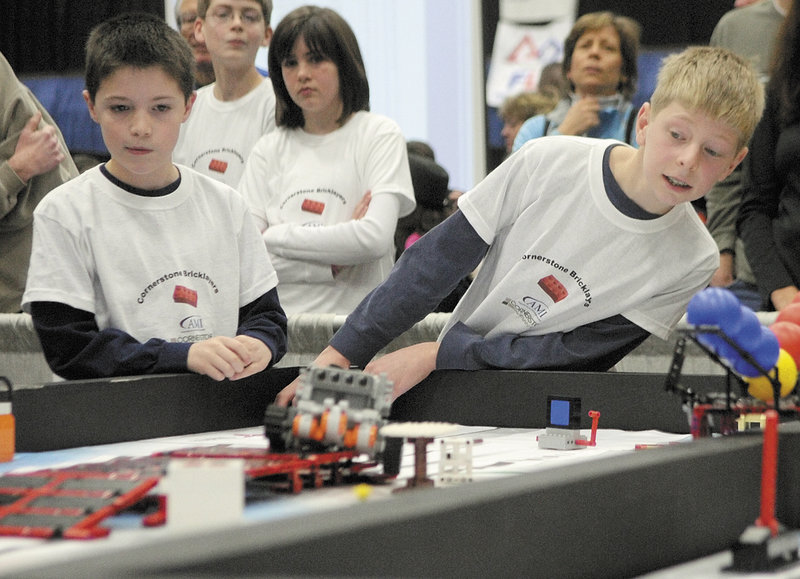 Preston Moody, left, and Isaac Lawrence watch their team's robot compete Saturday at the Maine FIRST Lego League Championship in Augusta.
