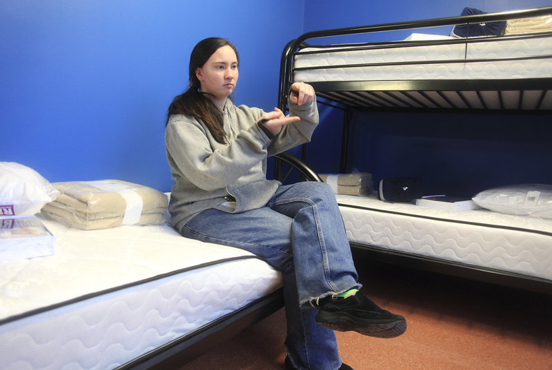 Crystal Swain, a homeless teen who has spent time at the Preble Street teen shelter, describes the width of the older shelter mattress compared to the new one she is sitting on.
