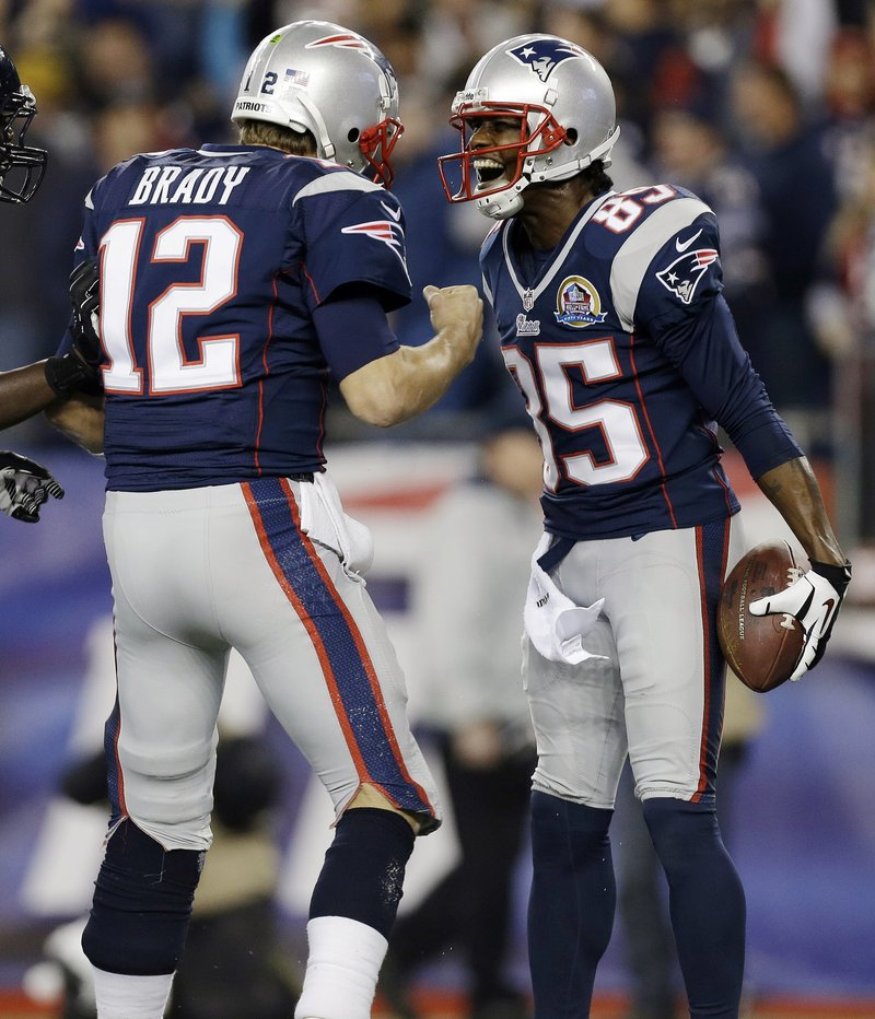 Brandon Lloyd celebrates his 37-yard TD catch with quarterback Tom Brady in Monday night's game at Foxborough, Mass. Brady threw four TD passes as the Pats dominated the Texans, 42-14.