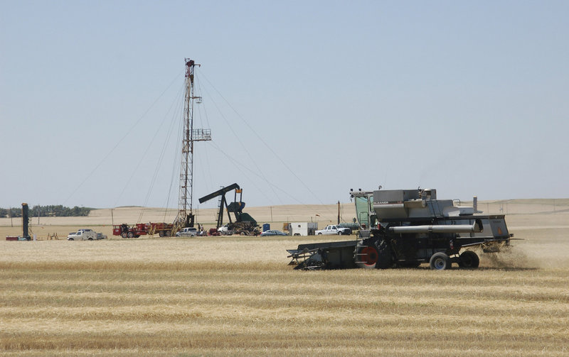 A combine cutting durum wheat near an oil well in Tioga, N.D. demonstrates the intersection of energy production and the environment. Critics of booming gas and oil production are concerned about the effects that pollution has on climate change generally, but also on the possible health consequences from breathing smog, soot and other pollutants.