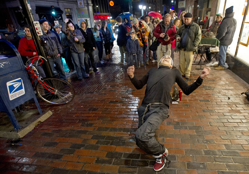 A small crowd gathers to watch Rafael Alvarez, a student at the Maine College of Art on Congress Street, dance to his boom box outside the school during the First Friday ArtWalk this month. Other street performers eat fire or play music and sing.