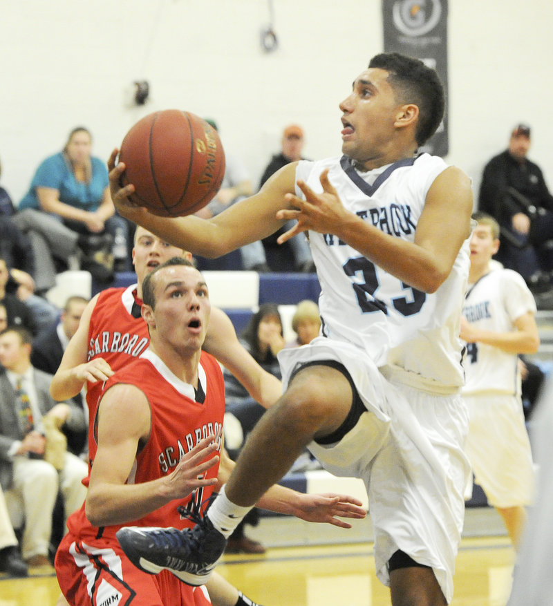 Keenan Lowe, who finished with 12 points for Westbrook, heads to the basket while driving past Dan Leclair of Scarborough.