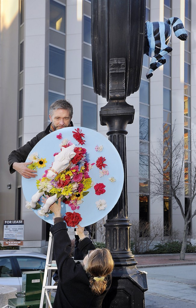 Scott Nash and Nancy Gibson Nash, owners of Nash Box Co., decorate the clock stand in Monument Square on Thursday with equestrian artwork donated by Kathleen Beecher of Peaks Island. The artwork, which changes every few weeks, is meant to call attention to a fundraising effort led by Portland Rotary and the Maine College of Art to replace the clock.