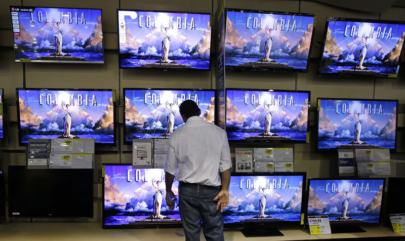 A shopper checks out televisions last month at a Best Buy store in Franklin, Tenn. The company, which is expected to get a purchase offer soon, has seen its stock price fall steadily since late June, closing Thursday at $14.12 per share.