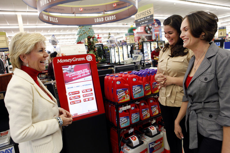 MoneyGram CEO Pam Patsley, left, discusses one of the company's self-service money transfer kiosks with Albertsons department store workers Amanda Boaldin, right, and Christina Plymale in Dallas, Texas, Nov. 15.
