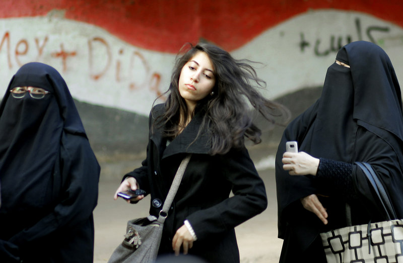 Egyptian women wait outside a Cairo polling station to cast their votes in a referendum on a disputed constitution drafted by Islamist supporters of President Mohammed Morsi.