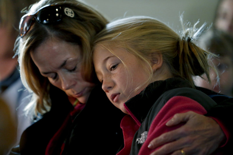"Molly Delaney holds her 11-year-old daughter, Milly Delaney, during a service at St. John's Episcopal Church on Saturday in honor of the victims of Friday's shootings at Sandy Hook Elementary School in Newtown, Conn. The effect of the shooting rampage on this western Connecticut town was deep and painful. ""Our wound is deep because we are a close-knit community,"" Patricia Llodra, the town's first selectman, told reporters. ""We truly care for each other."