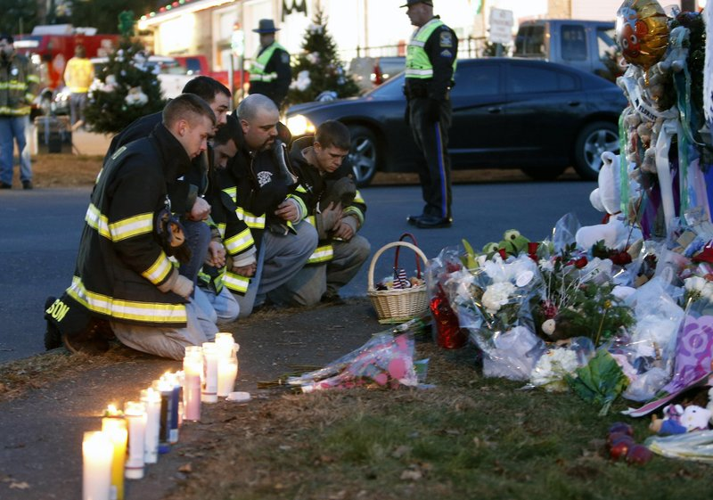 Firefighters pay their respects at a memorial for shooting victims near Sandy Hook Elementary School on Saturday in Newtown, Conn.