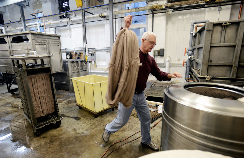 Don Morton, the dye master, carries yarn to a water extractor at the Saco River Dyehouse in Biddeford. Morton was the dye master at JCA in Massachusetts before it closed.
