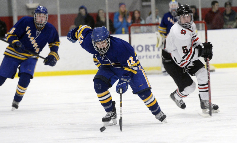 Andre Clement of Falmouth carries the puck up the ice as Scarborough defenseman Nick Bagley trails the play.