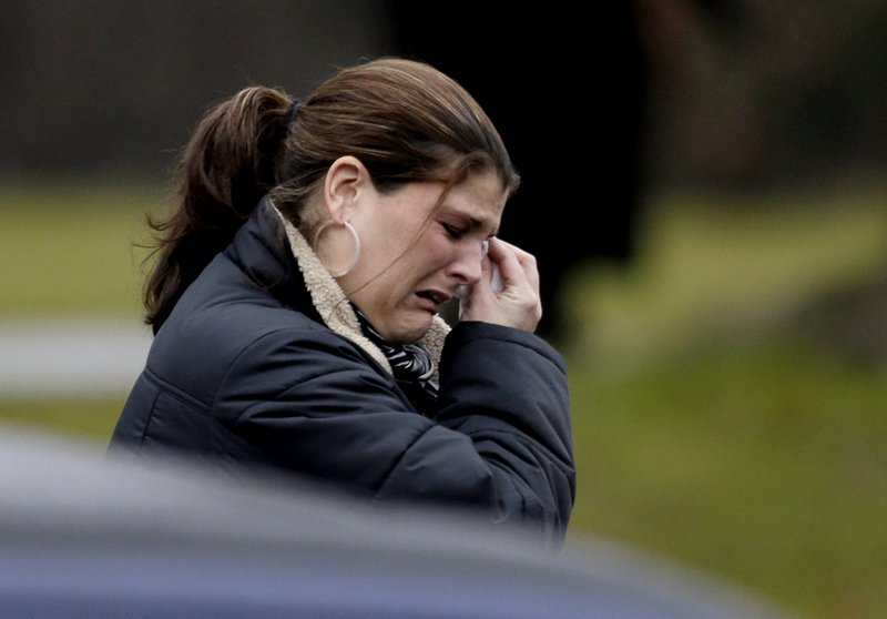 A mourner weeps at the funeral of a young Newtown, Conn., school shooting victim. Readers find fault with society and gun regulations.