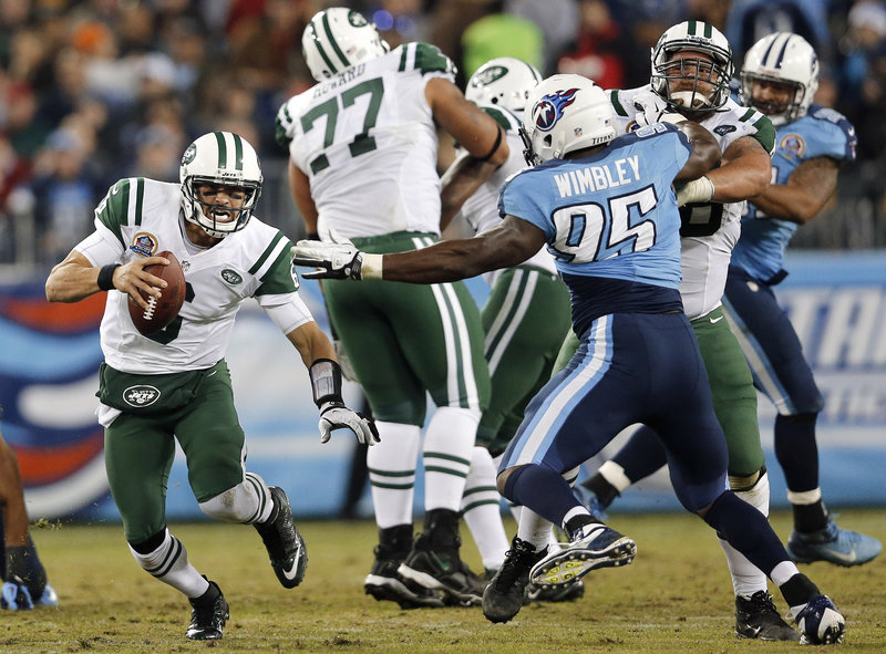 Jets quarterback Mark Sanchez scrambles away from Titans defensive end Kamerion Wimbley during Monday's game in Nashville, Tenn. Sanchez committed five turnovers, and the Jets were eliminated from playoff contention with a 14-10 loss.