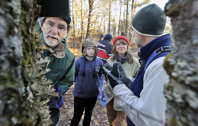 Joe Barth, left, inspects the lung lichen on a tree during a hike of two trails in the Hidden Valley Nature Center while retired teacher and volunteer Chuck Dinsmore, right, lectures to Hannah Lee Mencher and Sarah Wineberg.
