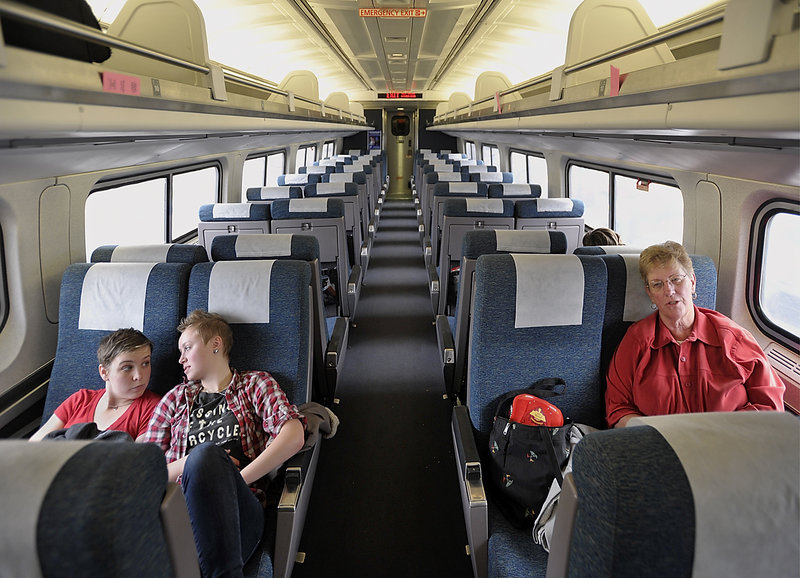 Kati Connelly of Brunswick, left, and Leah Petracca of Park City, Utah, who attend school in Boston, take the Downeaster on Wednesday to spend Christmas with Connelly's family. At right is Jean Townsend of Naples, Fla.