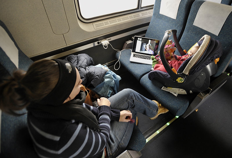 Wendelin Choiniere rides the Amtrak Downeaster on Wednesday with her daughter, Madison, 9 months, right, and son, Mason 2, sleeping on the seat to her left. They live in Brunswick and had made the trip to Exeter, N.H., for a pre-Christmas visit with Choiniere's mother.