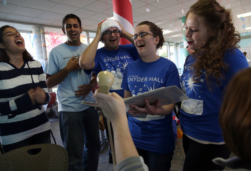 "University of Illinois students, from left, Katy Pippins, Warren D'Souza, Jose Cuevas, Clare Curtin and Kasia Stelmach sing ""Feliz Navidad"" for a ""Dial-a-Carol"" caller. Volunteers manning the 24/7 service during finals week fielded 500 calls on the first day this year."